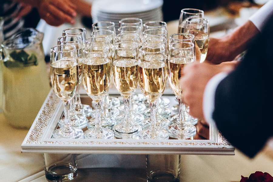 elegant people holding glasses of champagne at luxury wedding reception. hands taking drinks and toasting and cheering at social events. catering at christmas celebration